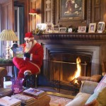 Santa reads in front of the fire